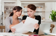 Two young women doing paperwork at kitchen table
