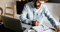 Portrait of busy bearded man in denim shirt and headphones checking planner at table with laptop.