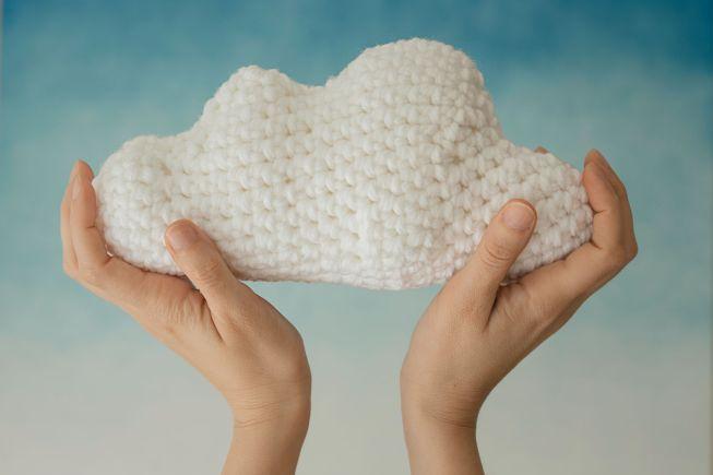 Hands holding an handmade amigurumi cloud on blue background.