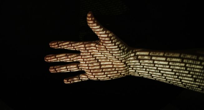 Internet programming concept of a human hand with binary code projected onto it.