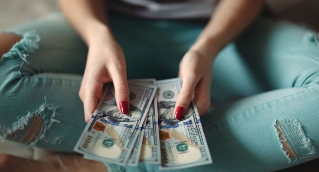 Closeup of woman hands counting new 100 US dollar banknotes