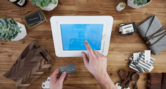 Artisan retail shop small business owner's hands ringing up a purchase on digital cash register with products around him