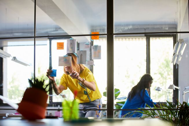 Businesswoman looking at adhesive note on glass door while colleague working in background