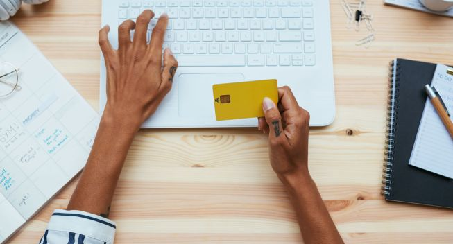 Overhead Of A Woman Shopping Online With Credit Card In Office.