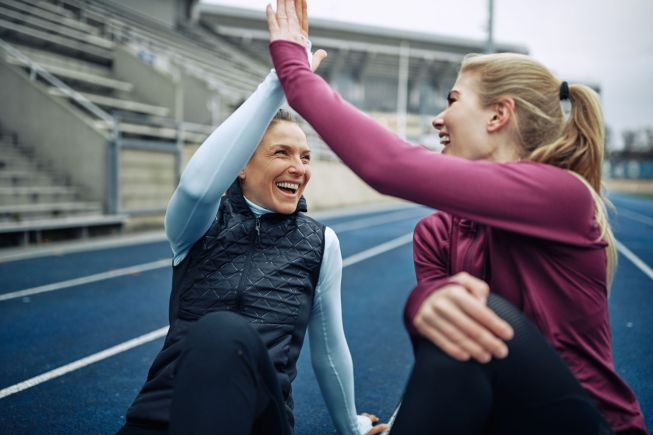 Two laughing women sitting on a track high fiving together after a run