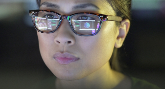 Close up stock image of a young asian woman staring at a computer screen which is reflected in her glasses. The reflection depicts graphs; people & data.