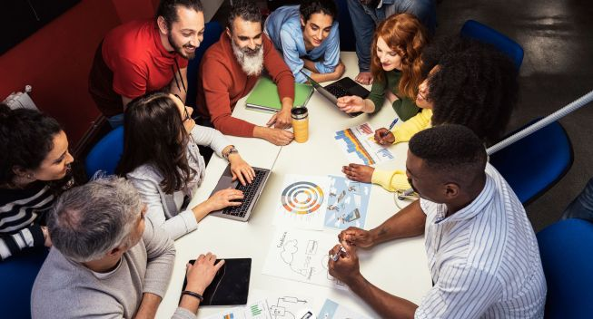 Successful team at work. Group of young business people working and communicating together in creative office