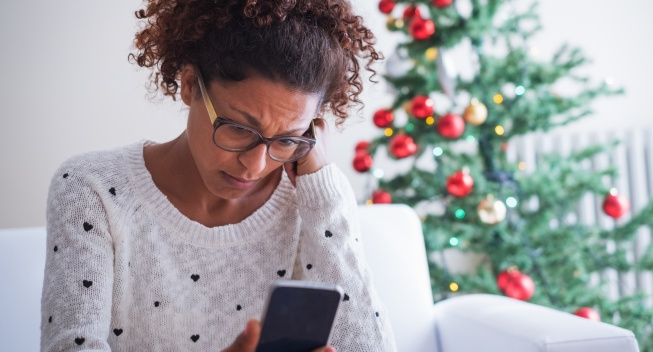 Stressed woman at home over the holidays looking at phone