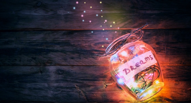 garlands colorful lights in glass jar with dreams, sparks, on old wooden table, retro toned