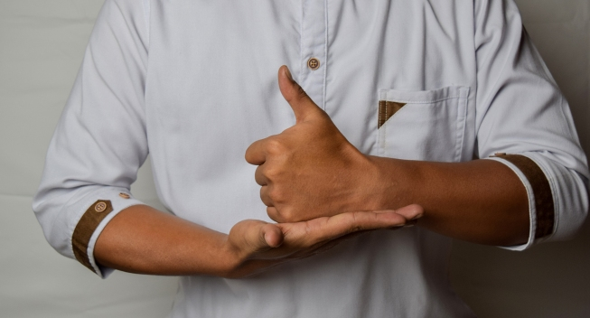 Close up Asian man shows hand gestures it means HELP isolated on white background. American sign language