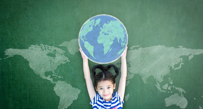 Educated school kid lifting world globe chalk doodle drawing on green chalkboard for education concept