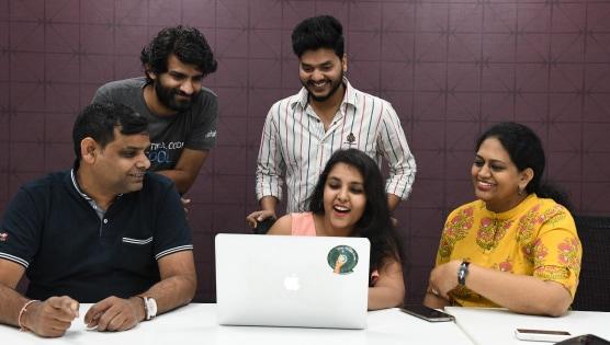 Employees huddling over laptop