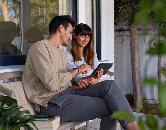 Couple sitting bench outside their house looking at a tablet