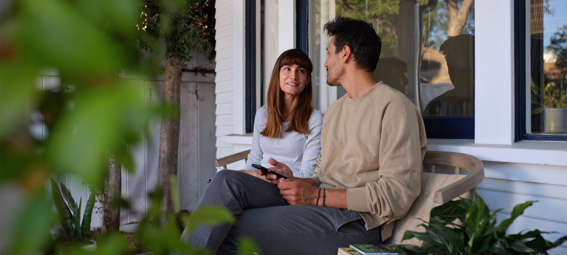 Couple sitting on a bench in front of a house