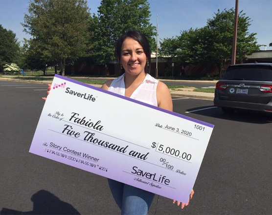 A woman holding her SaverLife check