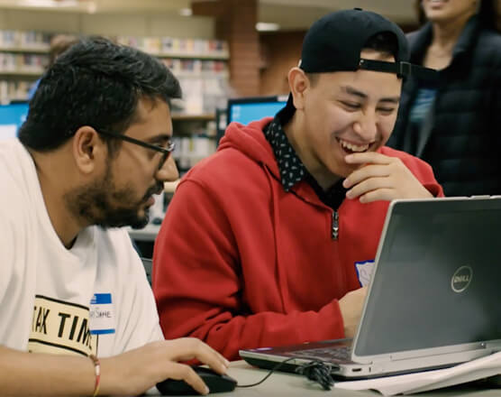 Two students laughing in front of laptop