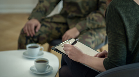 Intuit employee with a veteran writing on a notepad