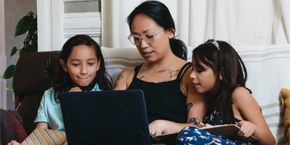 Woman and kids looking at laptopt