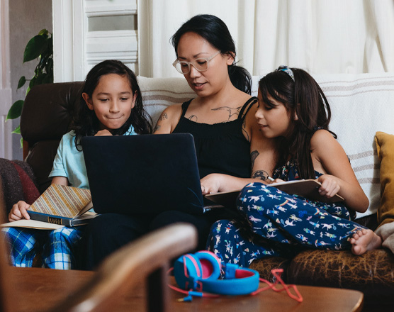 A mom and her kids reading from their laptop