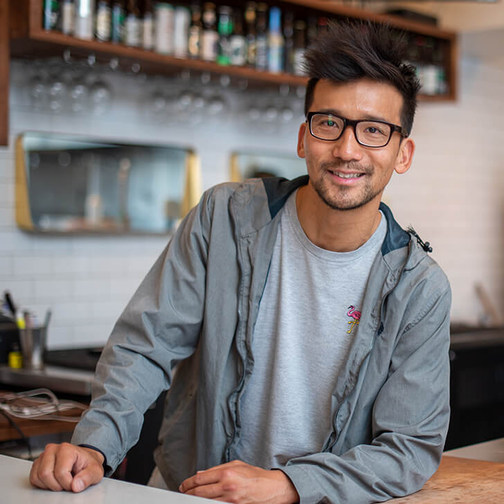 Small business owner behind the bar counter of his restaurant
