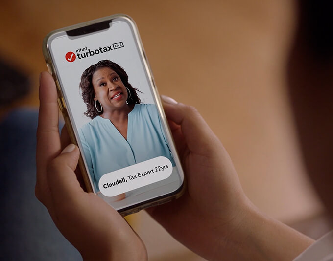 A person holding a phone that shows a TurboTax Live expert on the screen.