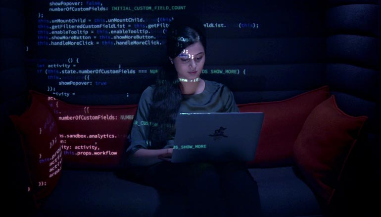 A woman sitting in front of her laptop writing codes