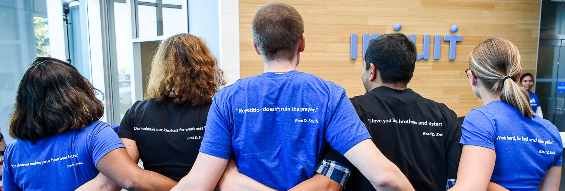 Employees wearing an Intuit shirt with Brad Smith quotes