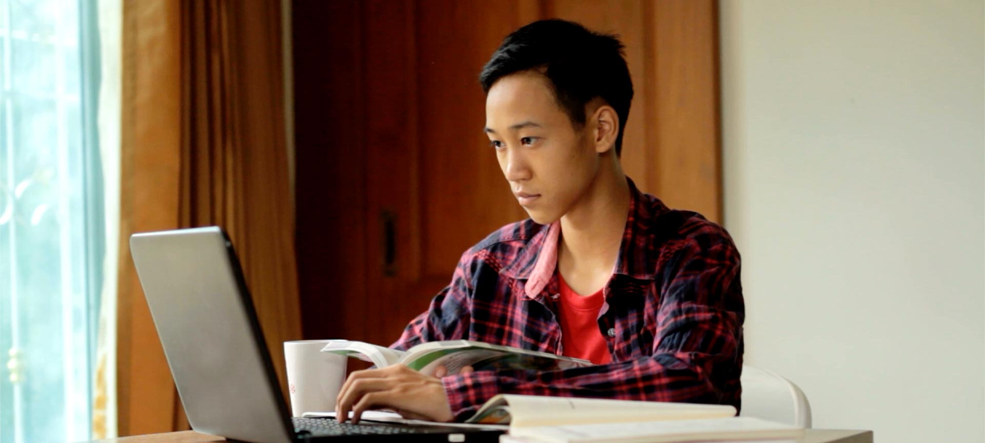 Male student using a laptop to study with book in hand