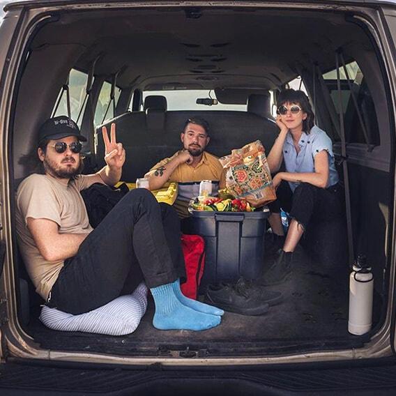 Wildermiss bad in the back of their van eating snacks